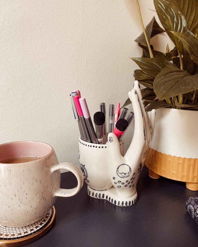 Close up of a hand-shaped pen pot.